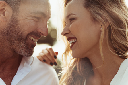 Close up of cheerful man and woman outdoors. Romantic couple together looking at each other and smiling. Banco de Imagens