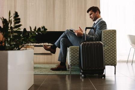 Zakenman die een tijdschrift leest tijdens het wachten op zijn vlucht bij de lounge van de luchtvaartlijnterminal. Ondernemer die op de wachtruimte van de luchthaven een tijdschrift leest.