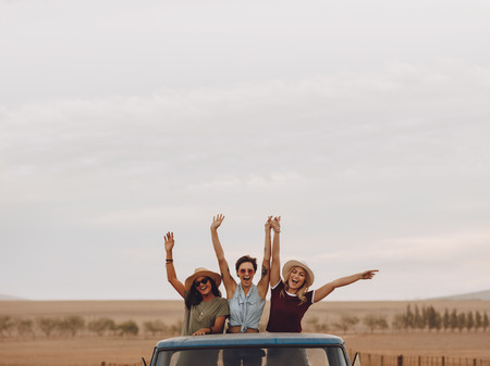 Group of friends on a roadtrip through countryside. Three young women standing in the back of a open truck laughing with their hands raised.