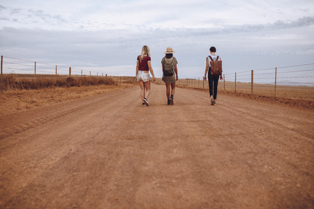Rear view of three young women walking down the country road. Female friends walking on a rural road.