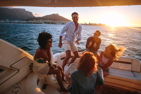 Group of young people dancing in boat party. Multiracial friends having fun in sunset yacht party.