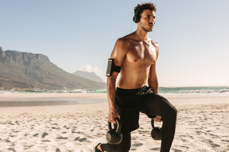 Man doing fitness workout at a beach using kettlebells. Bare chested athletic man doing exercise with kettlebells wearing wireless headphones and mobile phone fixed to armband.