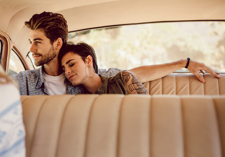 Young man and woman sitting on the backseat of a car. Couple traveling by an old car. Stock Photo