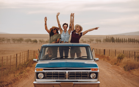 Group of female friends riding in pickup truck having fun on summer day. Three women standing at the back of pickup truck with their arms raises and smiling. Stock Photo