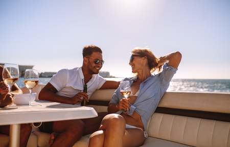 Smiling couple sitting on a boat with drinks. Relaxed young people during a boat party. Archivio Fotografico