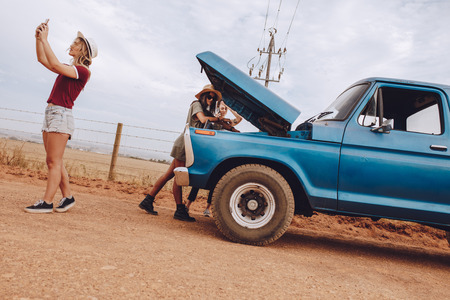 Female friends examining broken down car on country road. Woman looking under the hood of broken down car with friends searching for mobile network to make a phone call for assistance. Stock fotó
