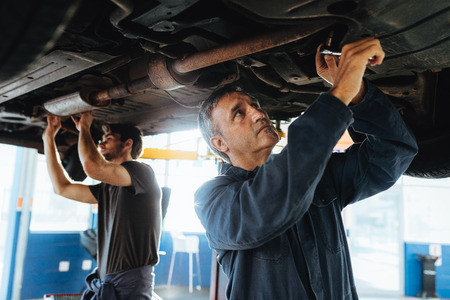 Two mechanics working under a car. Men in garage repairing exhaust system of a lifted automobile.