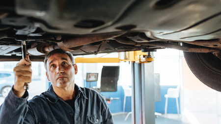 Experienced car mechanic repairing a lifted car in garage. Auto repair men fixing exhaust system of a car.