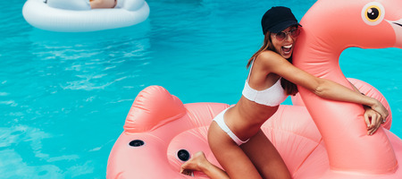 Horizontal shot of beautiful young woman in bikini smiling while floating on big inflatable flamingo. Girl having fun on floating toy in swimming pool.