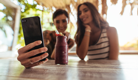 Two women sitting at a restaurant with a smoothie on the table taking photograph. Woman shooting selfie with a friend at a restaurant.