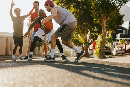 Men playing basketball game on a sunny day on an empty street. Men practicing basketball dribbling skills on street.