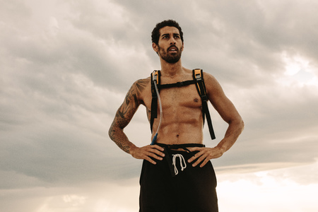 Strong and muscular man standing against cloudy sky and looking away with hands on his hips. Fit man with hydration pack taking rest after outdoor workout.