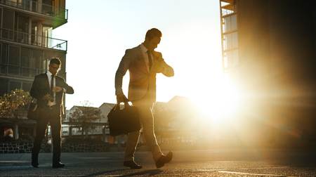 Men in formal clothes commuting to office early in the morning carrying office bags looking at their wrist watch. Businessmen in hurry to reach office walking on city street with sun flare in the background.