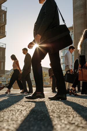 Men and women in formal clothes commuting to office in the morning carrying office bags. Business people walking to office on a busy city street with sun flare in the background.