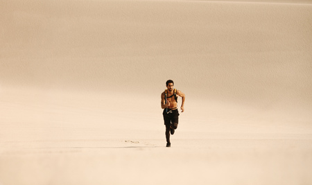 Healthy young man running over sand dunes and giving thumbs up. Fitness man running n desert. Stock Photo