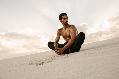 Athlete doing stretching exercises sitting on sand dune in evening. Runner sitting in desert with feet joined together and looking away.