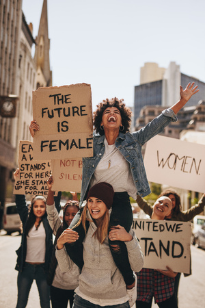 Group of protesters enjoying during a womens march with signboards. Laughing women holding protest signs for female future and empowerment.
