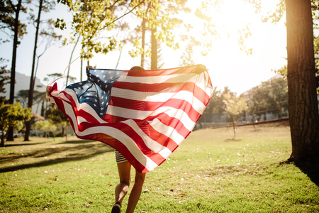 Woman running with american flag on a sunny day. Shot from behind of a girl running in the park with American flag.