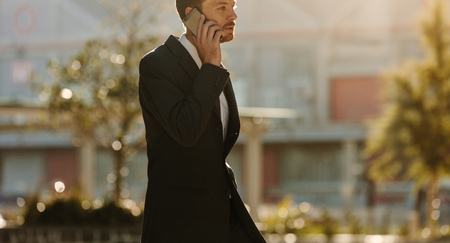 Businessman in formal clothes talking over mobile phone while walking on street. Busy office going person walking on street while talking on mobile phone.