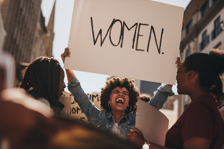 African woman holding a banner and laughing during women march. Group of female demonstrating outdoors with placards. Archivio Fotografico