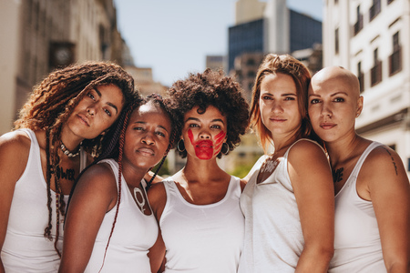Group of women in dress code demonstrating outdoors for women rights. Demonstrating stop domestic violence and abuse on women and give respect. Stock Photo