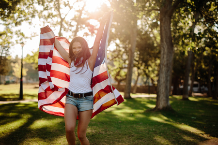 Attractive girl in shorts running with American flag in hands. Smiling young woman with USA flag at park. 写真素材
