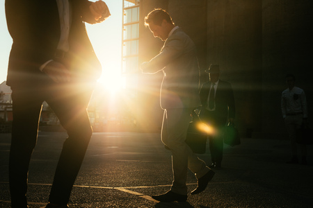 Men commuting to office early in the morning carrying office bags looking at their wrist watch. Businessmen in hurry to reach office walking on city street with sun flare in the background.