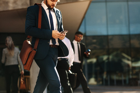 Businessman in formal clothes carrying office bag using mobile phone while commuting to office. Busy office going people using their mobile phones while walking on street.
