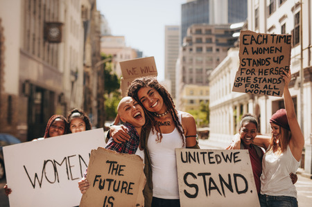 Young women holding banners and laughing during women march. Group of female demonstrating outdoors with placards and having fun. Stock Photo - 103720252