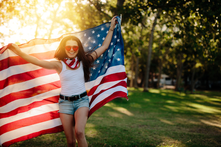 Girl in shorts running in the park holding American flag. Smiling girl with American flag at park on fourth of july.