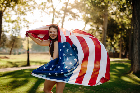 Patriotic girl with american flag in the park. Beautiful woman running with a USA flag outdoors at park.