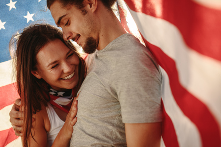 Couple in love with American flag around. Happy young man and woman under USA national flag.