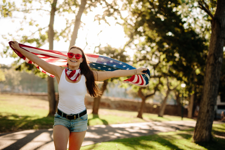 Portrait of patriotic american woman running with national flag in the park and smiling. Girl in park with USA flag in hands celebrating independence day.