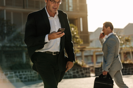 Businessman looking at his mobile phone while walking on street to office. Busy office going people carrying office bag and using mobile phone.