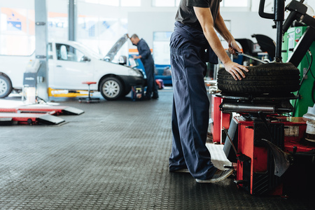 Car repair shop with mechanics working. Mechanic replacing tire of while on machine and other inspecting a vehicle.