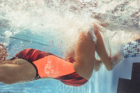 Shot of professional swimmer in action inside pool. Young woman turning over underwater from edge of pool while swimming. Stok Fotoğraf
