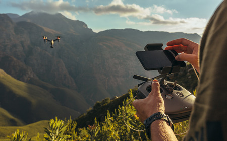 Close up of man flying a drone in green mountains and taking pictures. Focus on man hands operating drone flying remote controller with smart phone mounted on. Stock Photo
