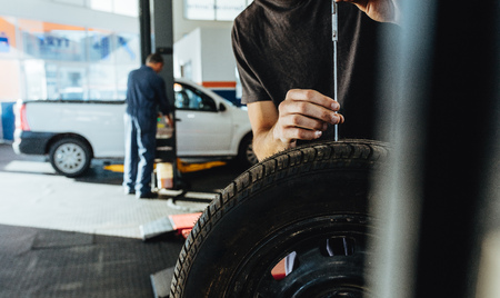 Mechanic checking car tire tread depth with caliber. Technician examining the car tire grip with a measuring instrument in service station.