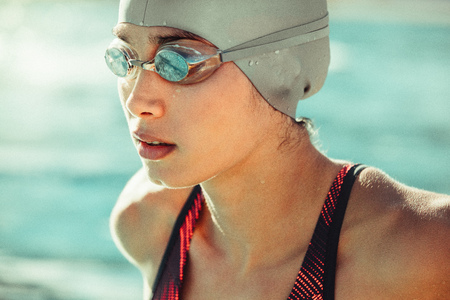Close up of young woman swimmer in swim cap and goggles. Focused professional swimmer looking away. Stock Photo