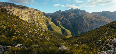 Wide angle shot of rocky mountain slopes and valley. Scenic mountains and valley in Jonkershoek nature reserve. 写真素材
