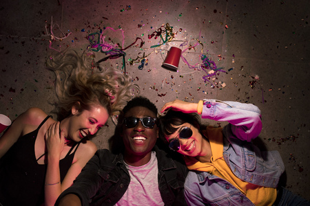 Top view of man and two women lying on floor and laughing at a house party. Friends lying on floor at the house party with cups and confetti around. Фото со стока