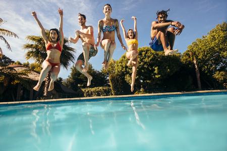 Amigos jóvenes felices saltando a la piscina al aire libre y divertirse. Grupo de hombres y mujeres saltando a la piscina de un resort de vacaciones.
