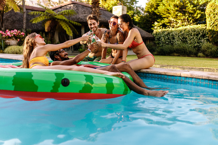 Multiracial group of friends having party in a private villa swimming pool. Men and women toasting beers at pool party.