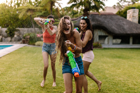 Women shooting at female friend with water gun. Happy female friends doing water gun battle near swimming pool outdoors.