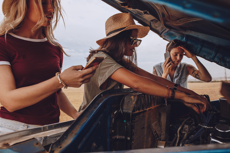 Woman trying to fix the car with friends making phone calls for help. Woman trying to repair the car on highway on a road trip with friends.
