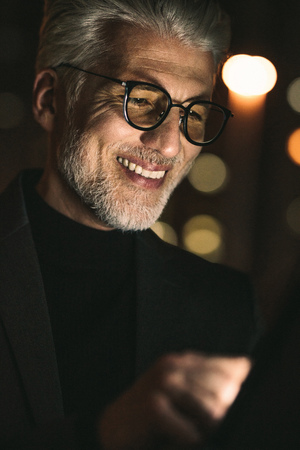 Close up of smiling businessman using digital tablet in office. Mature man working late night in office with tablet pc.