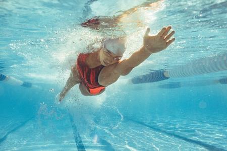 Unterwasseraufnahme der Sportlerin, die im Pool schwimmt. Junge Frau, die die Front kriecht, kriechen in einem Pool.