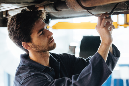 Close up of young car technician checking the electrical wires under the car. Mechanic repairing the car in auto repair shop. Imagens