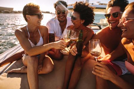 Gruppe junger Männer und Frauen, die auf dem Yachtdeck sitzen und Getränke rösten. Junge Leute, die auf einem Boot mit Getränken feiern. Standard-Bild