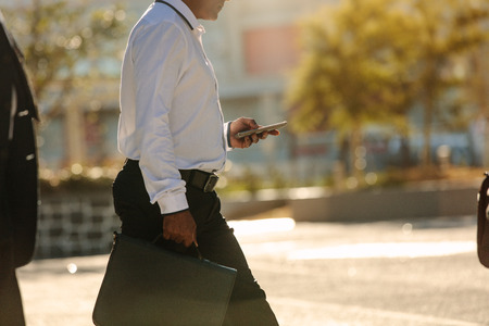 Businessman using mobile phone while commuting to office. Busy office going person walking on street carrying his office bag looking at his mobile phone.